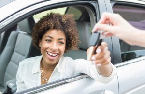 a woman happily taking the keys to her brand new car